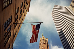 Shot of three buildings taken looking upward. Behind them, you can see the blue sky with a few clouds. The building in the forefront is to the left of the screen, tan, and has large windows. On a pole strung from the side is an American flag. The flag hangs limply. To the right of the frame, a tall metallic looking building with cross-cross panels of light and dark fills the sky. Behind the flag, in the background, is a tiered building that has a turret and tower at the top.