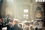 Image of unfocused people in the midst of soft light from unseen windows inside a beautiful cathedral.