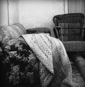 Image of a porch with a wicker chair and a floral couch with a blanket over it in black and white.
