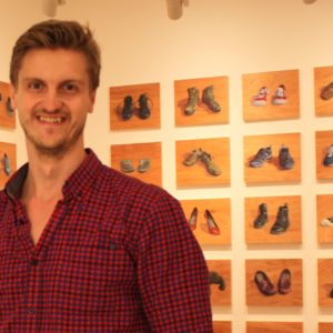 photo of Alastair John Gordon standing in front of a gallery wall with orange paintings set up in a grid (5x5) on the wall, slightly blurred out. He is smiling, wearing a plaid black and red button up with thin black lines. He has a slight beard and is smiling.