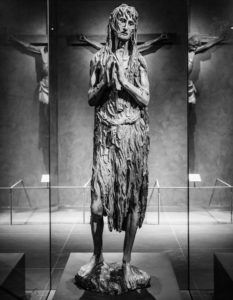 Image of Donatello's Mary Magdalene sculpture. Mary is standing slightly to her left side, with her hands clasped together. She is looking off towards the right of the frame, slightly, and looks haggard, and is wearing a ragged dress.