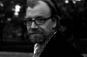 Photo of George Saunders in b&w looking at the camera. He has a gentle expression on his face, but his eye contact is direct. His hair is balding a bit with a tuft on top of his head. He's wearing dark, thick rimmed rectangular glasses, a dark jacket, and a pattern shirt underneath.