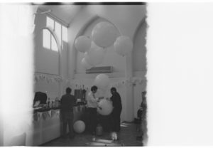 Black and white film image of the interior of a large white-wooden walled church, with high vaulted ceilings and large windows at the top of the walls. There are three enormous white balloons floating near the ceiling. To the left of the room is a table set up with things on top of it (maybe food). Several people stand in the center, holding a large balloon, and helping set up. The left and right side of the image is a blank strip of light from the film being exposed to light.
