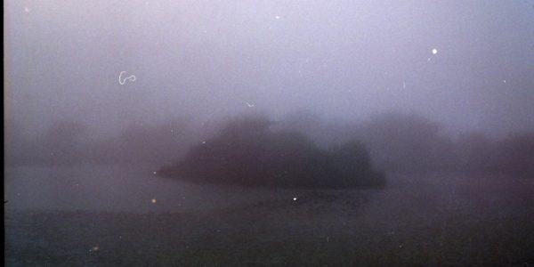 a purple tinted image of a little island in a lake surrounded by deep green, hilly land on the edges. the image is very foggy, hazy, looks wet.