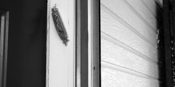 black and white image of a mezuzah on the door post of a house.