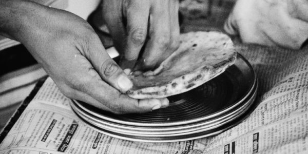 black and white image of hands buttering a piece of naan on a stack of thin silver plates atop a table covered with newspaper.