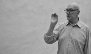 Black and white photo of Sean Scully from chest up. He is wearing a button up shirt with the sleeves rolled up, and is gesturing with his hand. He has dark glasses on, is bald, and has a calm expression on his face.