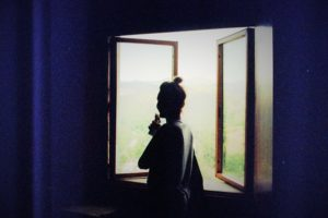 silhouetted image of a woman standing in front of a window, mostly in dark. outside it is bright, light, and airy, inside you can only see the silhouettes of things. the windows open outwards, the image feels hopeful.