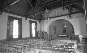 black and white image of a large hall filled with chairs and an altar at the front, presumably a church, that is completely empty.