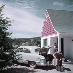 vintage image of a man unpacking the trunk of a car while a woman stands under the awning of a cabin while holding a baby.