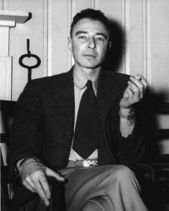 Portrait of Robert Oppenheimer reclining a chair with his legs crossed, holding a cigarette in a very cavalier manner.